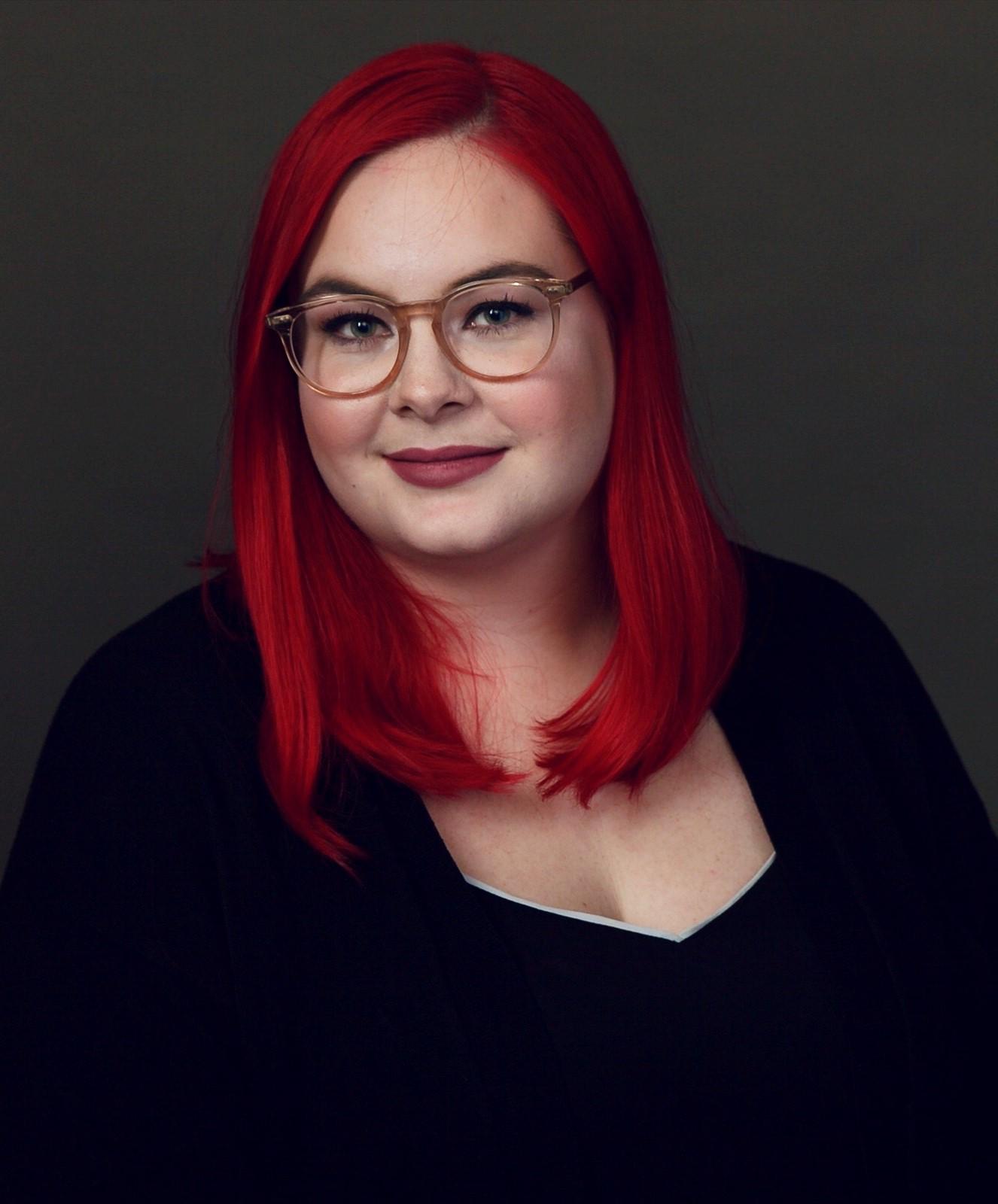 Une femme blanche aux cheveux rouge vif et portant des lunettes sourit à la caméra, sur arrière-plan foncé. / Caucasian and bespectacled woman with bright red hair smiling at the camera on a dark background.