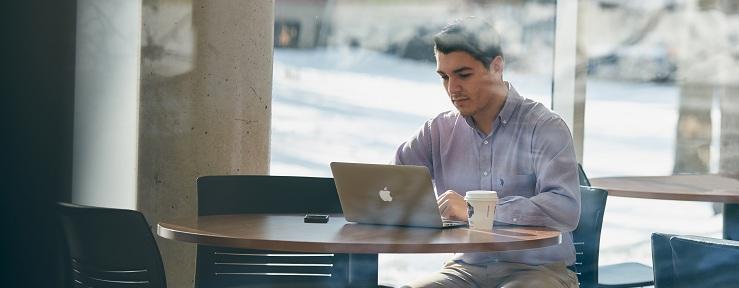 Jeune homme assit à une table ronde avec son ordinateur